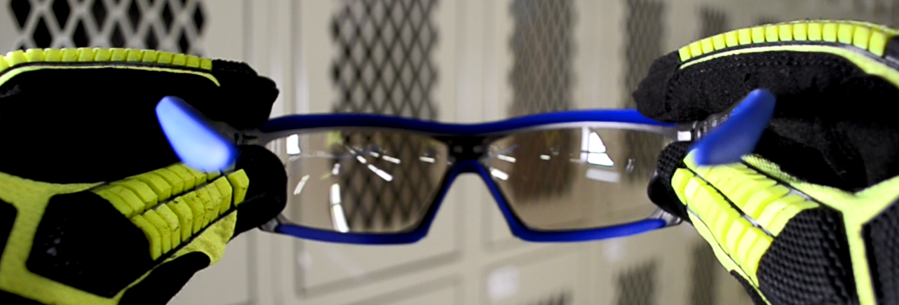 Image of a worker holding a pair of safety glasses
